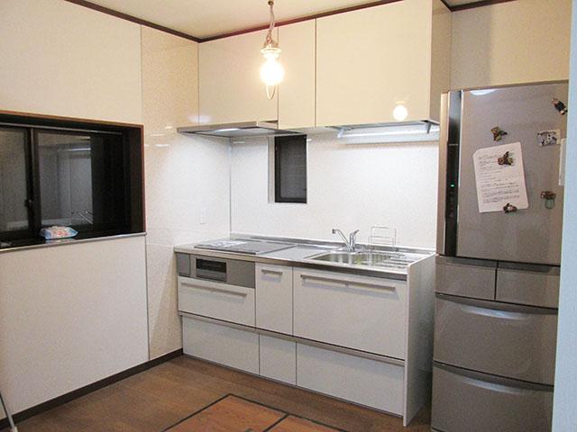 白が基調の明るいI型キッチンになりました。コンロはIHコンロをお選びいただきました。 奥様はあまり背が高くないため、吊戸棚が使いづらいということでハンドムーブという吊り戸部分の収納を手で引いておろせるものを取り付けました。レンジフードもスリムなタイプをお選びいただいたのでキッチン全体の見た目がすっきりとしました。